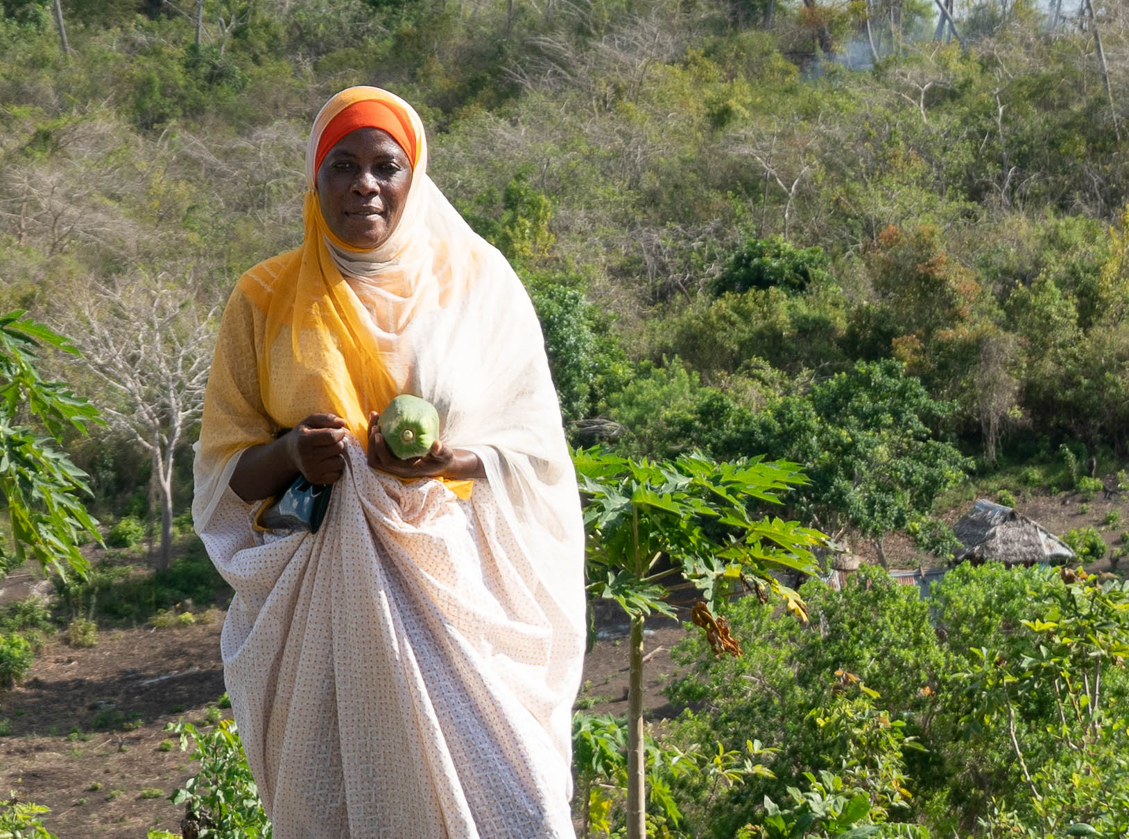Woman in on a hillside in Tanzania holding her purse and a papaya