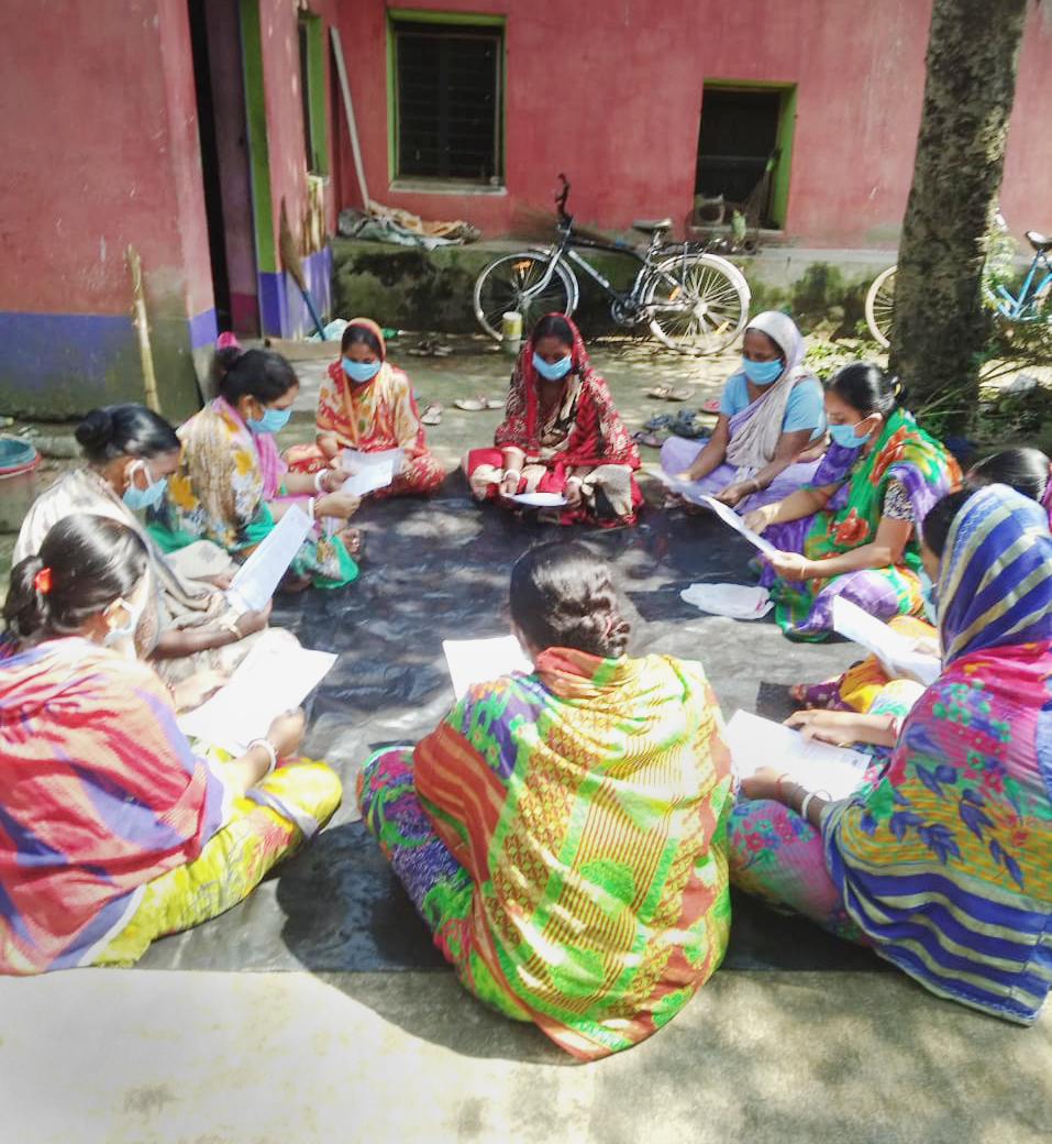Women in India sitting in a circle with masks on